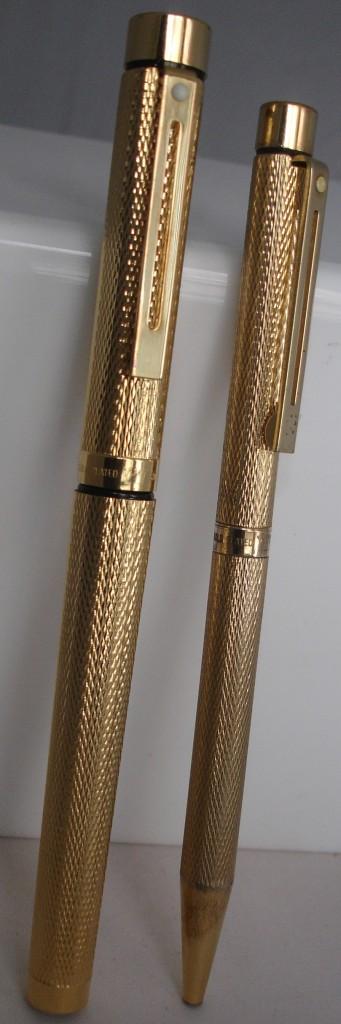 Pareja de estilográfica y bolígrafo de la serie Targa. Ambos vienen ornamentados con un patrón de motivos de granos de maíz y cebada (barleycorn).