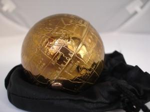 Polvera de los años cincuenta con un diseño esférico que imita la forma del planeta Tierra
