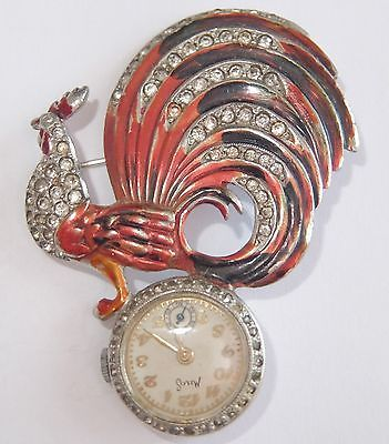 Raro broche de Boucher de un gallo esmaltado del que pende un reloj. Fuente: www.ebay.com